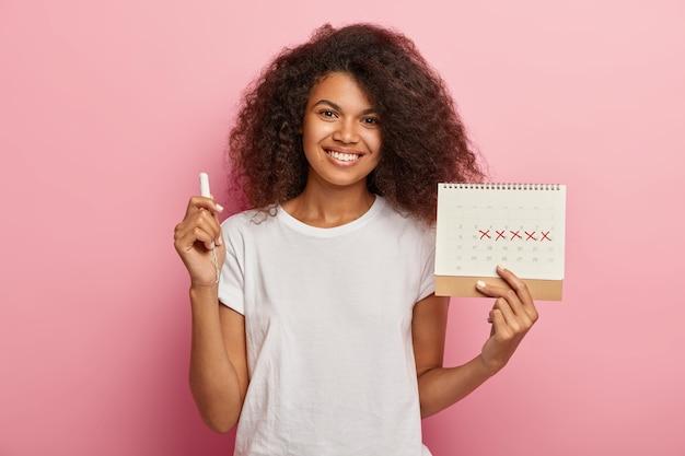 Счастливая кудрявая дама держит календарь менструаций с отмеченными днями после полудня и тампон, одетая в повседневную белую футболку, изолированную на розовом фоне