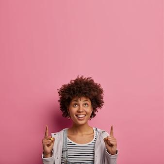 행복한 곱슬 머리는 놀라운 제안을 제공하고, 즐거워 보이며, 위쪽을 가리키며, 이빨 미소를 지으며, 멋진 판매를 기뻐하고, 캐주얼 한 옷을 입고, 장미 빛 벽에 포즈를 취하고, 재미있는 이벤트에 참석할 것을 제안합니다.