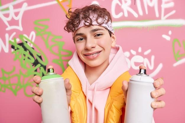 Happy curly haired teenage boy dressed in sweatshirt and vest holds two aerosol sprays enjoys creating street art on walls has favorite hobby has braces on teeth