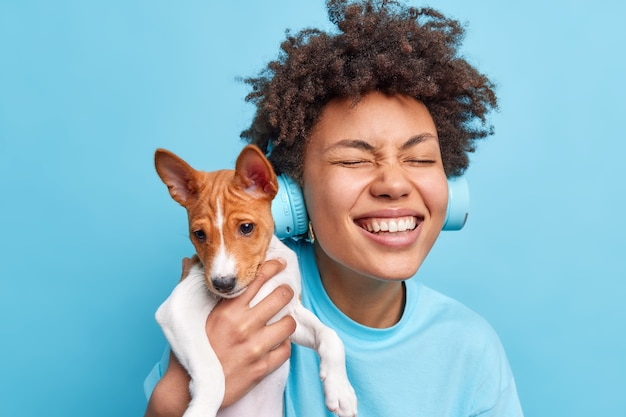 Happy curly haired teenage girl plays with pedigree dog enjoys company of favorite dog have walk together closes eyes wears stereo headphones listens music dressed casually isolated on blue wall