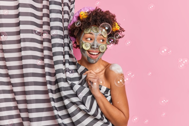 Happy curly haired woman applies clay mask with cucumber slices enjoys showering looks aside positively poses half naked behind curtain has rubber ducks in hair isolated over pink background