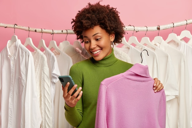 Happy curly haired woman chooses clothes, holds comfortable jumper on hangers, white outfits on racks in background, messages via mobile phone.