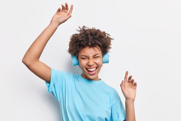 カジュアルなtシャツを着た幸せな巻き毛の女性が腕を上げて、白い壁に隔離されたポジティブな感情を表現する良質のステレオヘッドホンで音楽を聴くのを楽しんでいます。