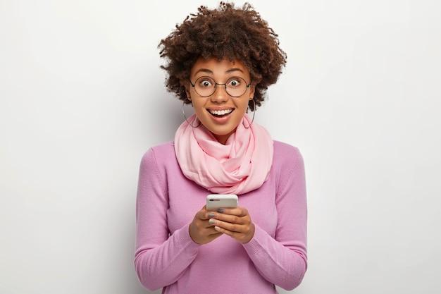 Felice donna dai capelli ricci tiene cellulare moderno, chat online, sorride con gioia, indossa occhiali trasparenti e maglione viola casual