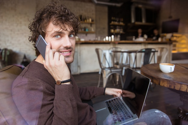 Happy curly handsome attractive smiling man in brown sweetshirt sitting in cafe using laptop and talking on cellphone