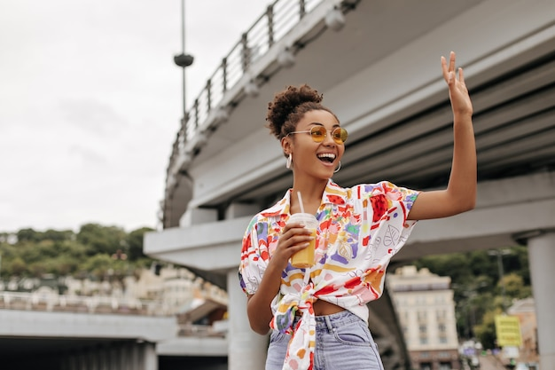 Happy curly lady in denim pants and colorful shirt waves hand in greeting