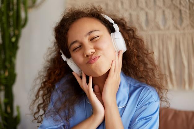 Felice mulatta riccia giovane donna seduta sul letto, ampi sorrisi e occhi chiusi, ascoltando la canzone preferita in cuffia, godendosi la musica e la domenica mattina.