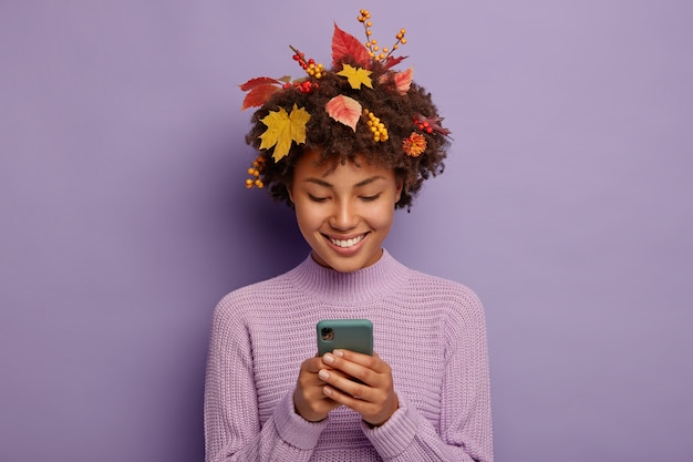 Happy curly woman chats with friends via cellular, has tender smile, has yellow leaves on head