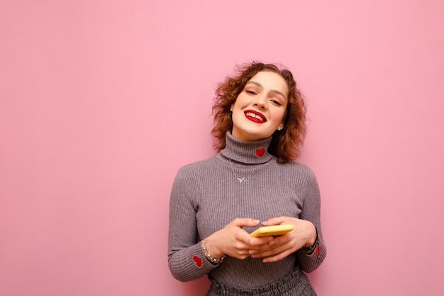 회색 스웨터에 행복 곱슬 여자는 그녀의 손에 스마트 폰으로 서