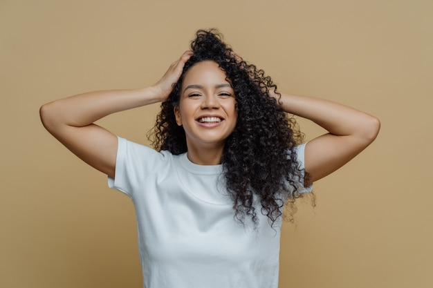Happy curly woman keeps hands on head