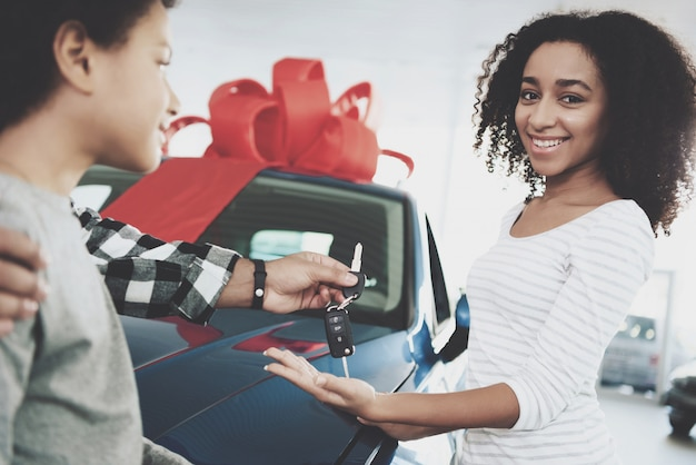 Happy curly woman receiving auto takes car keys.