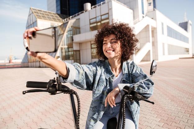 屋外の現代的なバイクに座って幸せな巻き毛の女性