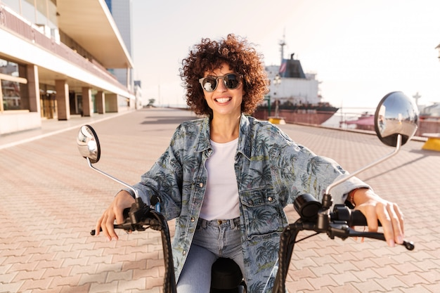 Happy curly woman in sunglasses rides on modern motorbike