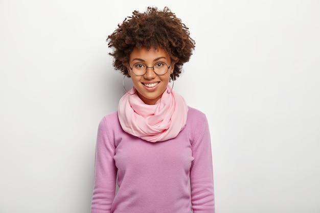 행복한 곱슬 여자는 안경과 보라색 옷을 입고 멋진 하루를 즐기고 부드럽게 미소 짓습니다.