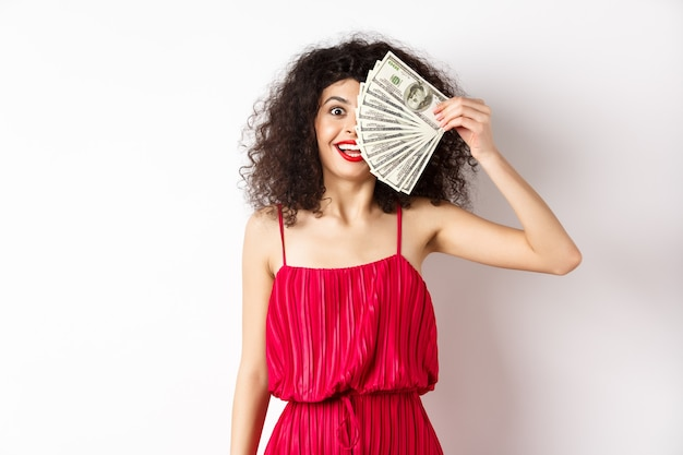 Happy curly woman winning money, holding dollar bills on half of face, smiling excited, standing in red dress on white background.