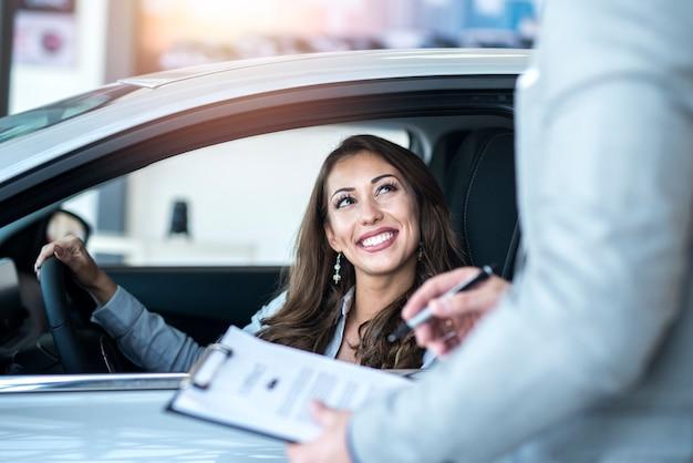 地元の自動車販売店で真新しい車を購入する幸せな顧客