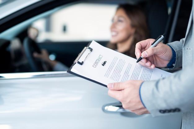 Cliente felice che acquista un'auto nuova di zecca presso un concessionario di automobili locale