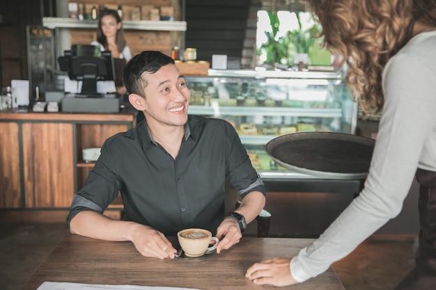 幸せな顧客はウェイトレスによって彼のコーヒーを提供されます