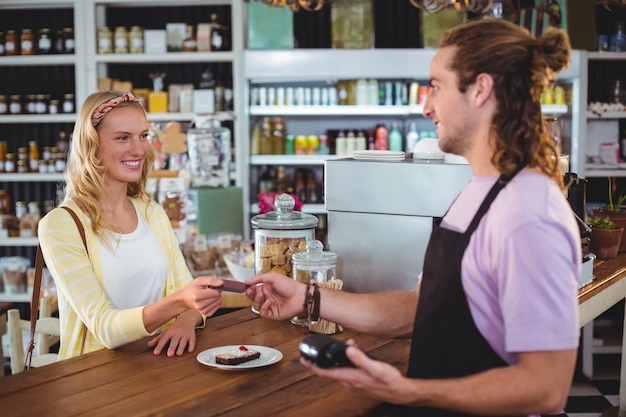 Happy customer giving credit card to waiter