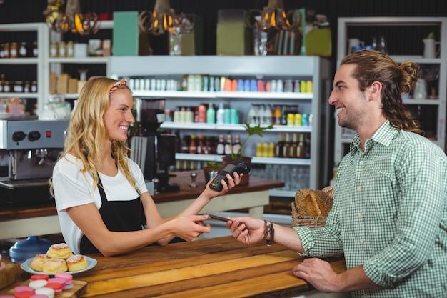 Happy customer giving credit card to waitress