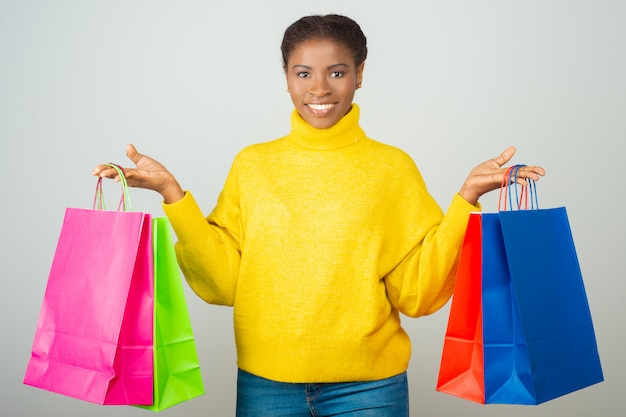 Happy customer holding and showing colorful shopping bags