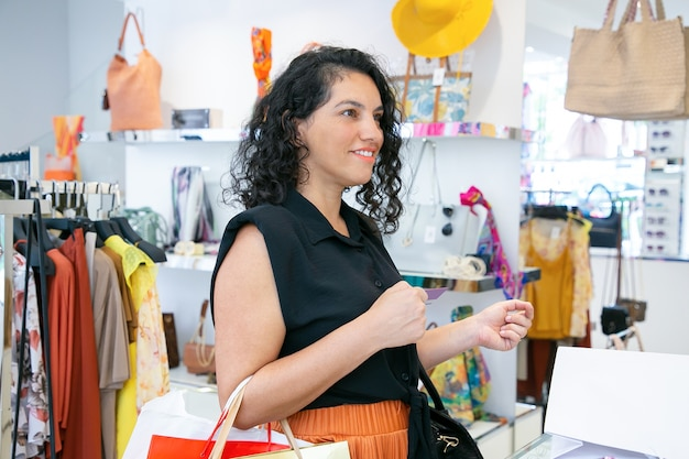 패션 스토어에서 구매를 지불하는 행복한 고객. 쇼핑백과 신용 카드를 들고 여자입니다. 미디엄 샷. 쇼핑 컨셉