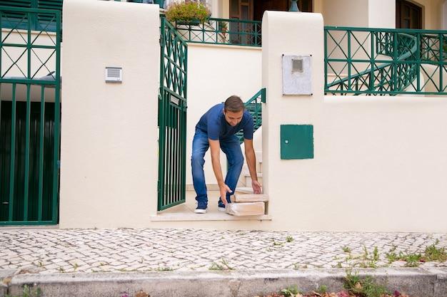 행복한 고객이 주문을 받고 지상에서 가져옵니다. 골판지 패키지를 받고, 야외에서 서서 앞으로 구부리는 백인 중년 클라이언트. 배달 서비스 및 포스트 개념