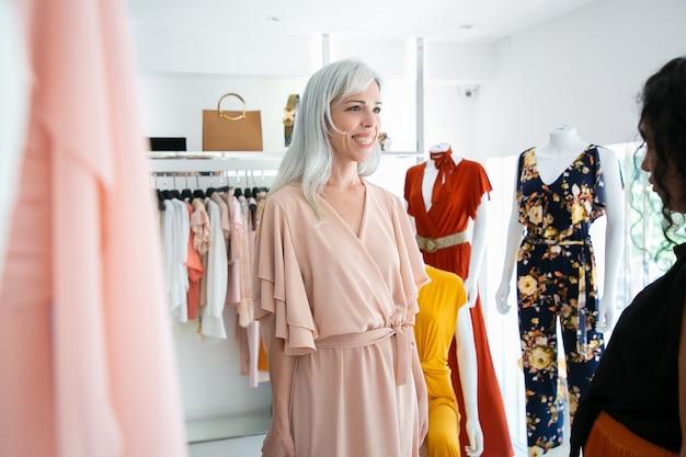 Счастливый клиент примеряет новое платье в бутике. женщина выбирает одежду в магазине модной одежды. покупка одежды в концепции бутика