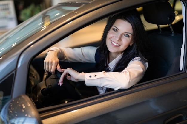取引センターで新しい車を買って幸せな顧客の女性。