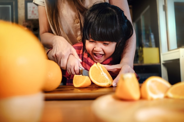 Happy cute 3-4 years old girl with her mom slice some orange on wooden table in pantry room.