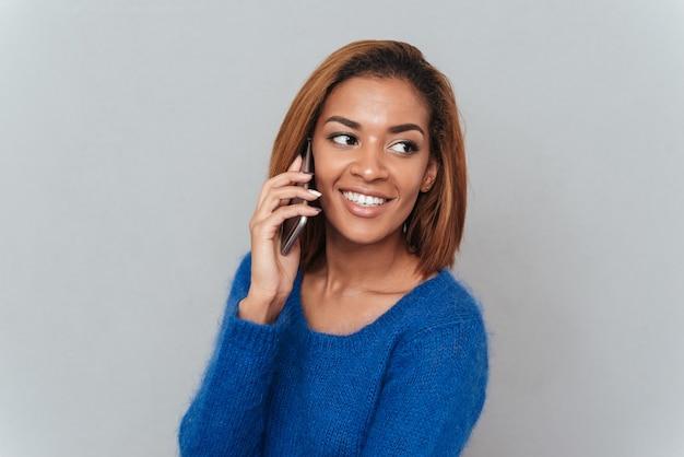 파란색 스웨터를 입은 귀여운 아프리카 여성이 전화 통화를 하고 옆을 바라보고 있습니다. 격리 된 회색 배경