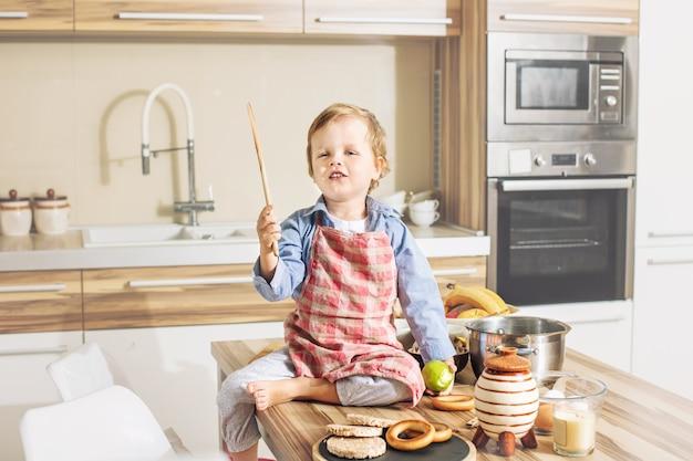 행복하고 귀엽고 아름다운 아이가 부엌에서 놀면서 집에서 웃고 있다