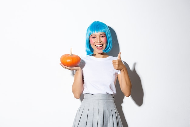 Happy cute asian girl celebrating halloween, wearing party costume and wig, holding small pumpkin, showing thumbs-up in approval.