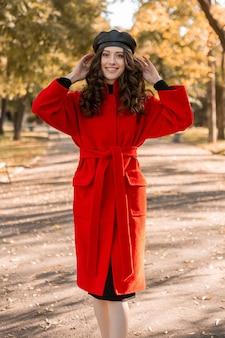 따뜻한 빨간 코트 가을 유행 패션, 거리 스타일을 입고 공원에서 산책하는 곱슬 머리를 가진 행복 귀여운 매력적인 세련된 웃는 여자, 베레모 모자를 쓰고