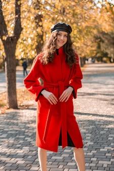 暖かい赤いコートの秋の流行のファッション、ストリートスタイル、ベレー帽の帽子をかぶって公園を歩いている巻き毛の幸せなかわいい魅力的なスタイリッシュな笑顔の女性