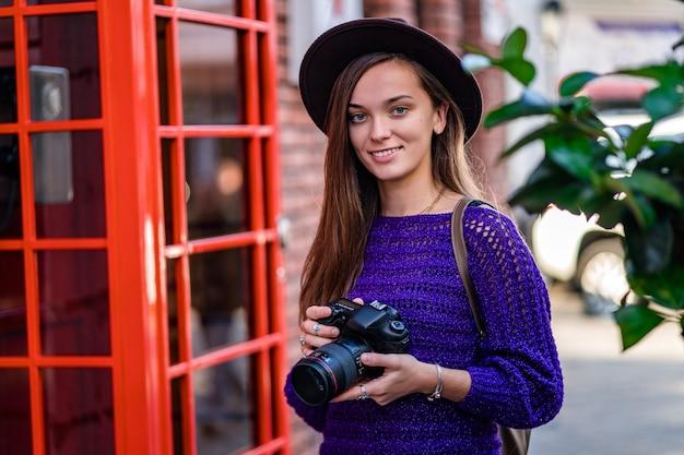 Счастливый милый привлекательный фотограф молодой женщины в шляпе с камерой во время прогулки по городу