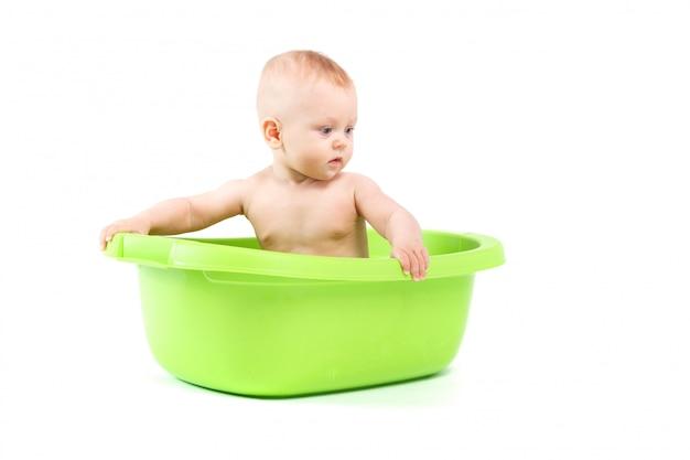 Happy cute baby boy take bath in green tub