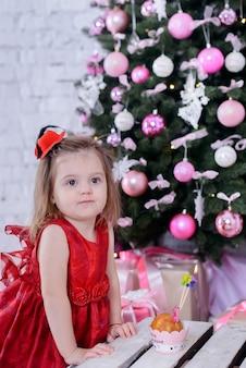 クリスマスツリーの近くの幸せなかわいい女の赤ちゃん
