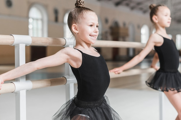Happy cute ballerina girl practicing at barre