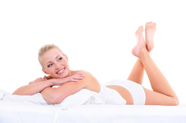 부드러운 침대에 누워 행복 귀여운 아름 다운 웃는 여자