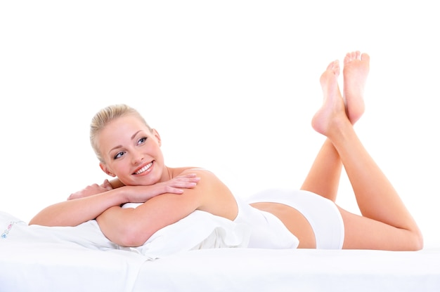 Happy cute beautiful smiling woman lying on the soft bed