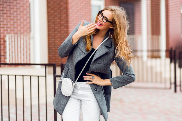 Happy cute blond woman in stylish coat wolking outdoor.