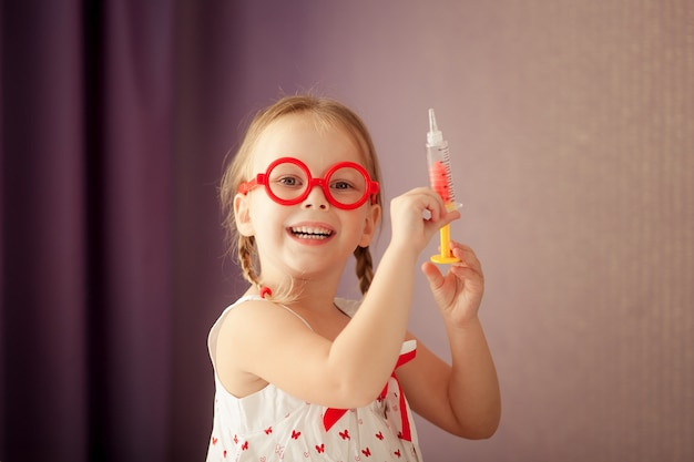 Happy cute blonde girl with braids and wearing red glasses plays a doctor