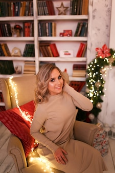 暖炉のそばで休んでいるホームドレスの笑顔と肘掛け椅子に座っている木の幸せなかわいいブロンドの女性