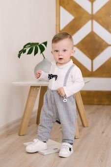 Happy cute boy in a gentleman's suit stands