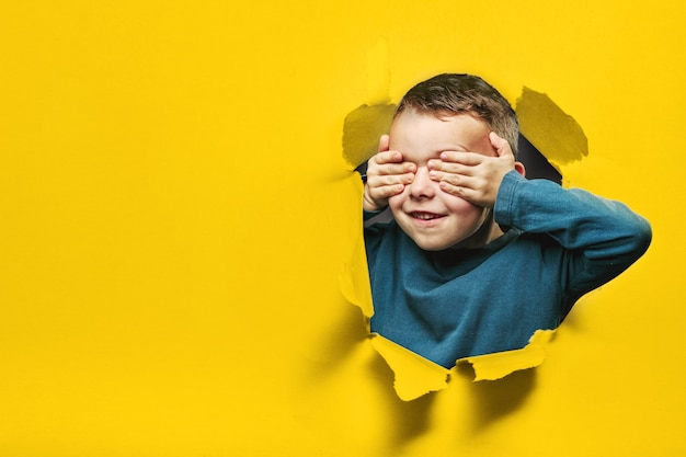 Happy cute boy is having fun played on black background wall. climbs through a hole in the paper. bright photo of a boy.