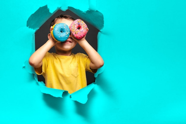 Happy cute boy is having fun played with donuts on blue