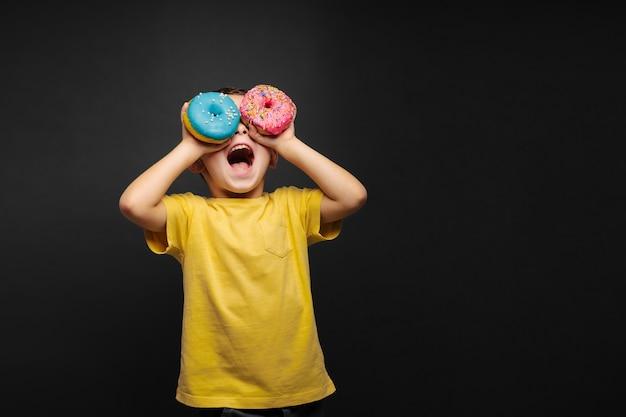 幸せなかわいい男の子は黒のドーナツで遊んで楽しんでいます