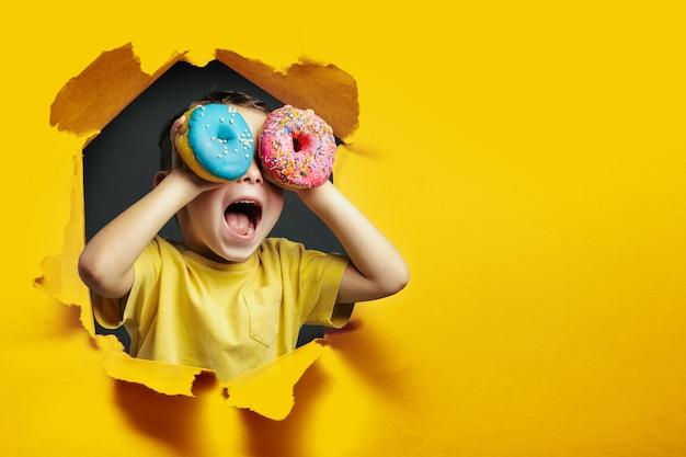 행복한 귀여운 소년이 노란색 배경 벽에서 도넛을 가지고 즐겁게 놀고 있습니다