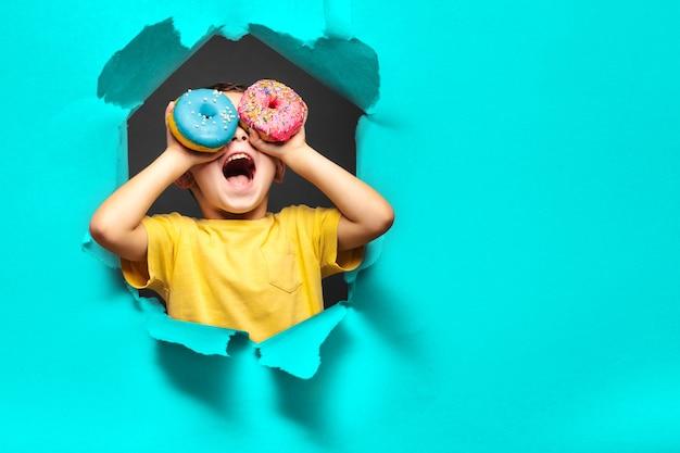 幸せなかわいい男の子はドーナツで遊んで楽しんでいます